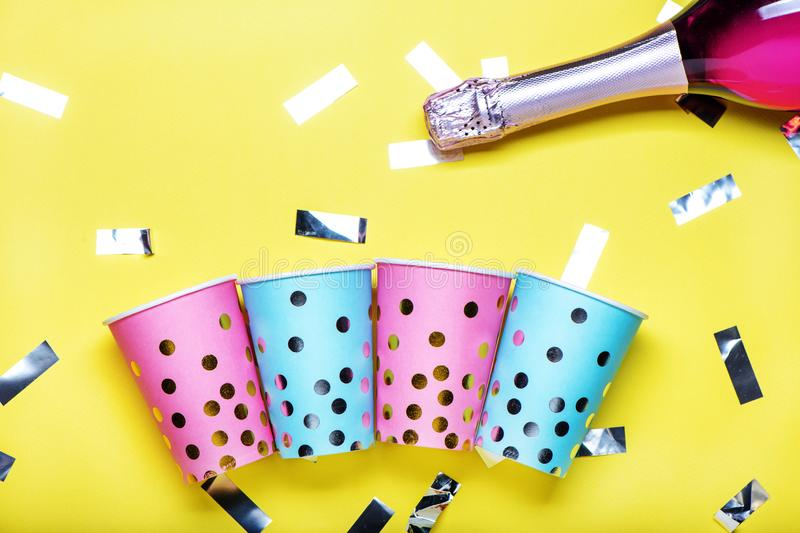 Blue and pink polka dot paper cups on yellow background. stock image