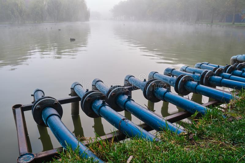 Blue pipes connected into a city pond, on a foggy morning, at Alexandru Ioan Cuza IOR park, Bucharest, Romania.  stock images