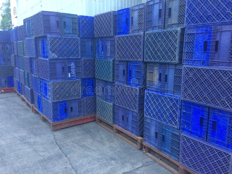 Blue plastic basket used in agriculture. Warehouse background stock photos