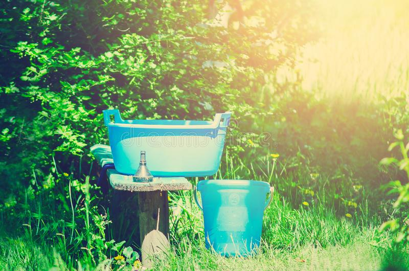 A blue plastic bucket and trough stand on the street. Housekeeping in a country house. Russia stock photo