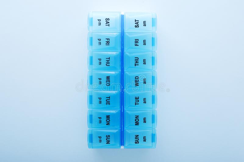 Blue plastic 14 day pill box with pills on blue background. Top view stock photo