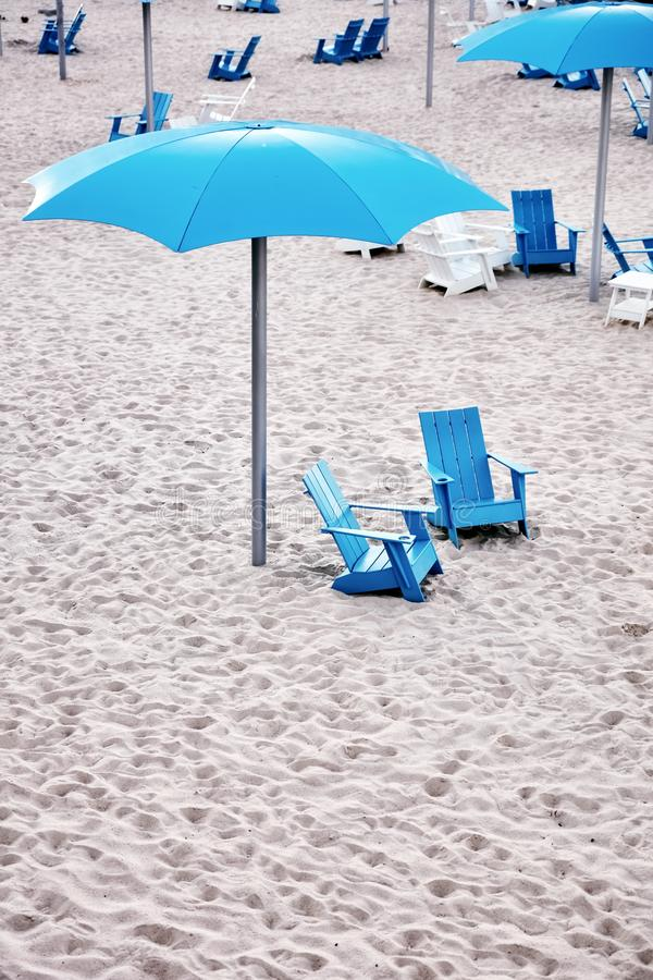 Blue plastic deck chairs and cyan plastic umbrella on the sands of a beach. Blue plastic deck chairs and cyan plastic umbrella on the white sands of a beach royalty free stock images