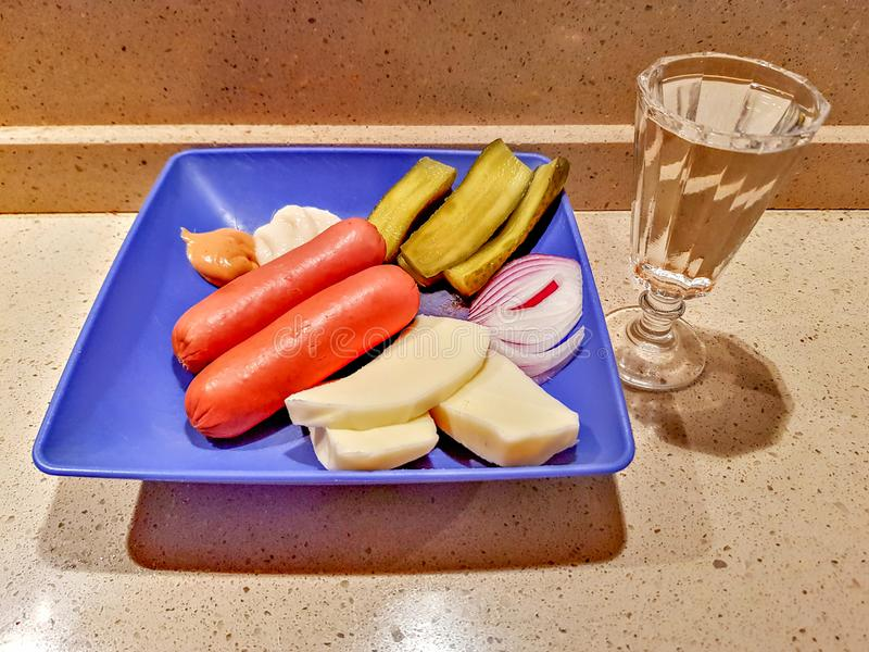 A glass of vodka, sausages, cucumbers, onions, cheese and sauces royalty free stock photo