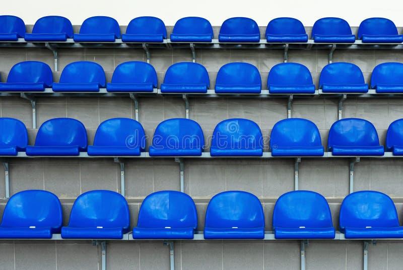 Blue plastic seats in the stadium. Tribune fans. Seats for spectators in the stadium royalty free stock photo