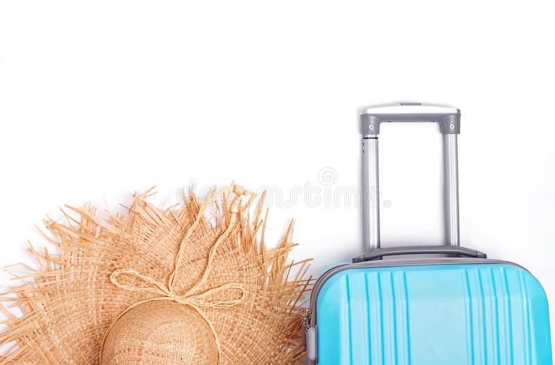 Blue plastic suitcase and straw hat isolated on white background. stock photography