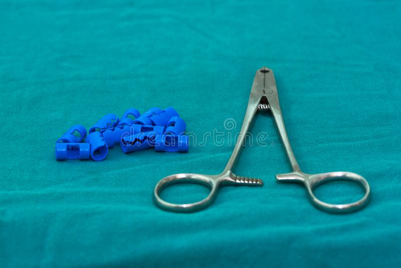 Blue plastic surgical clips and stainless applier for scalp hemostasis in brain surgery on green table in operating room stock images