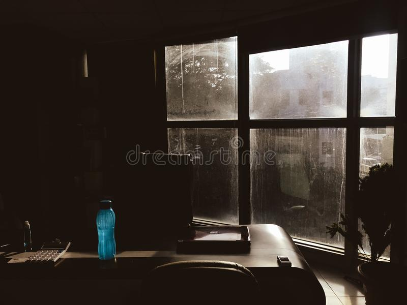 Blue Plastic Tumbler on Wooden Table Beside Chair in Room royalty free stock photos