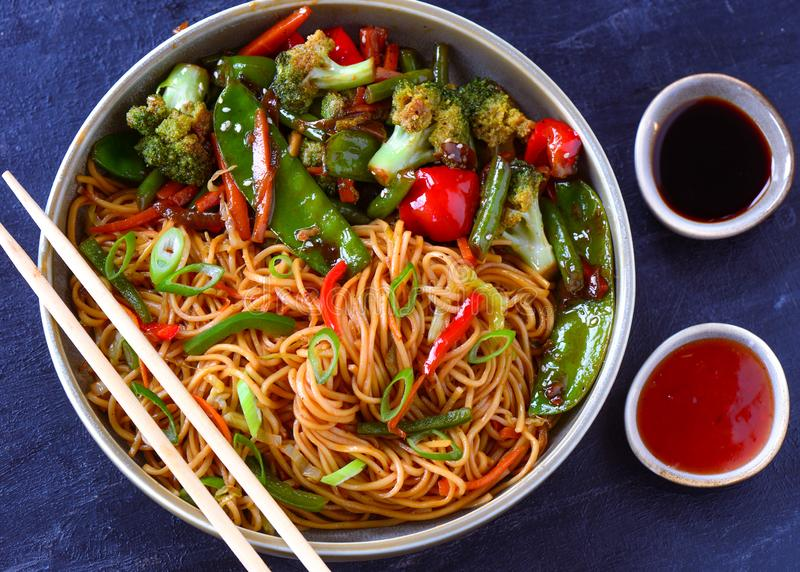 Malay cuisine Hakka noodles with stir fry veggies. Blue plate ceramic made  raisins   s pottery clay   birthday party fresh clean eating homemade anniversary stock photography