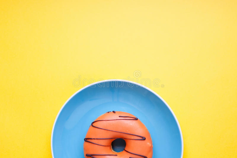 Blue plate with an orange donut in the glaze on a yellow background. Top view with copy space. Minimal concept stock photo