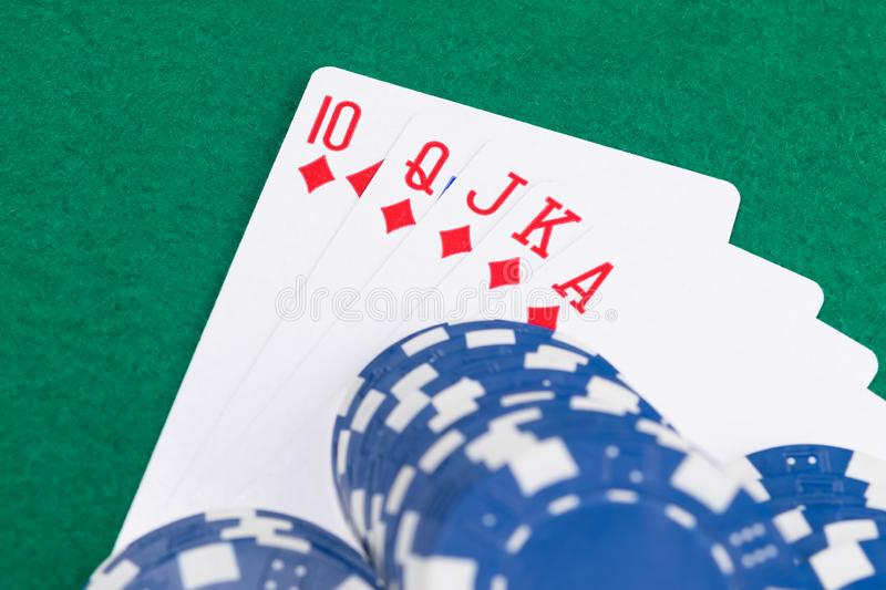 Blue poker chips lay on a combination of cards on a green table background stock images