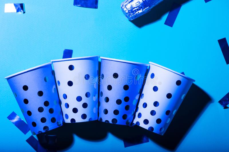 Blue polka dot paper cups and straws in ultraviolet light stock photos
