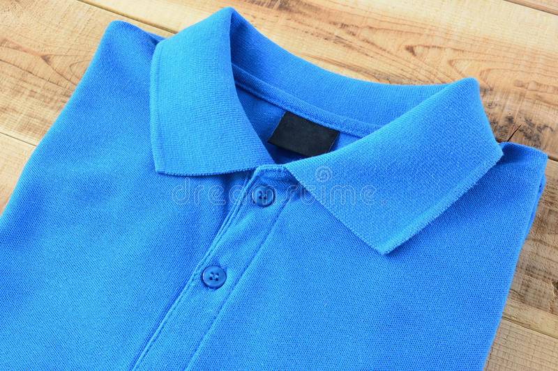 Blue Polo T-shirt on wooden. Close up blue polo t-shirt on wooden stock photos