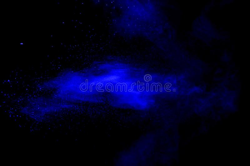 Blue powder explode cloud on black background. Launched blue dust particles splash on background stock images