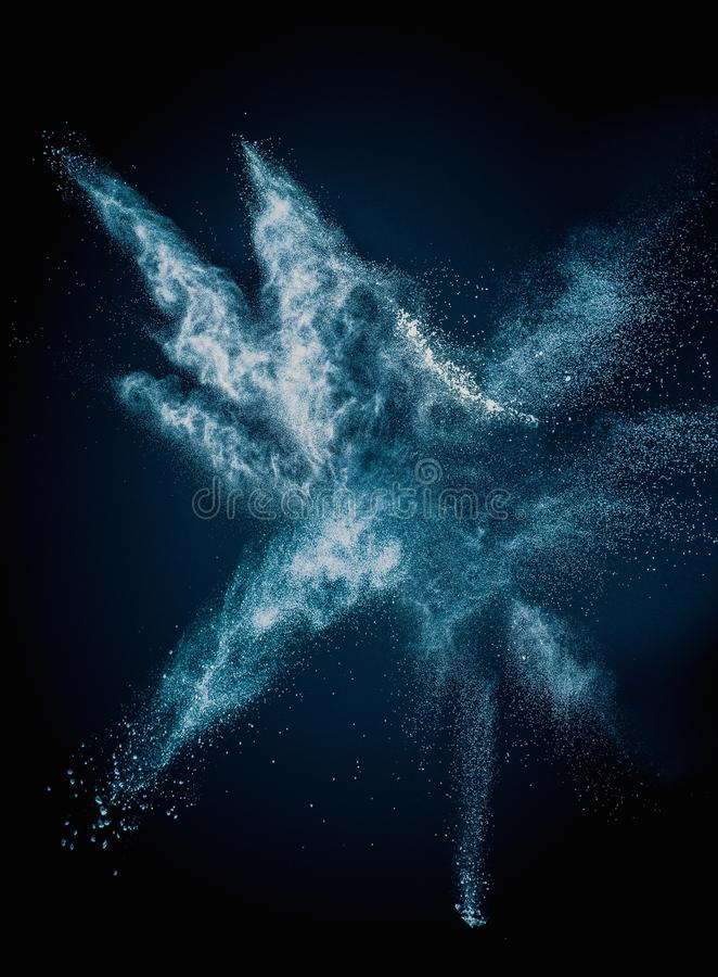 Blue powder exploding. Isolated on black stock images