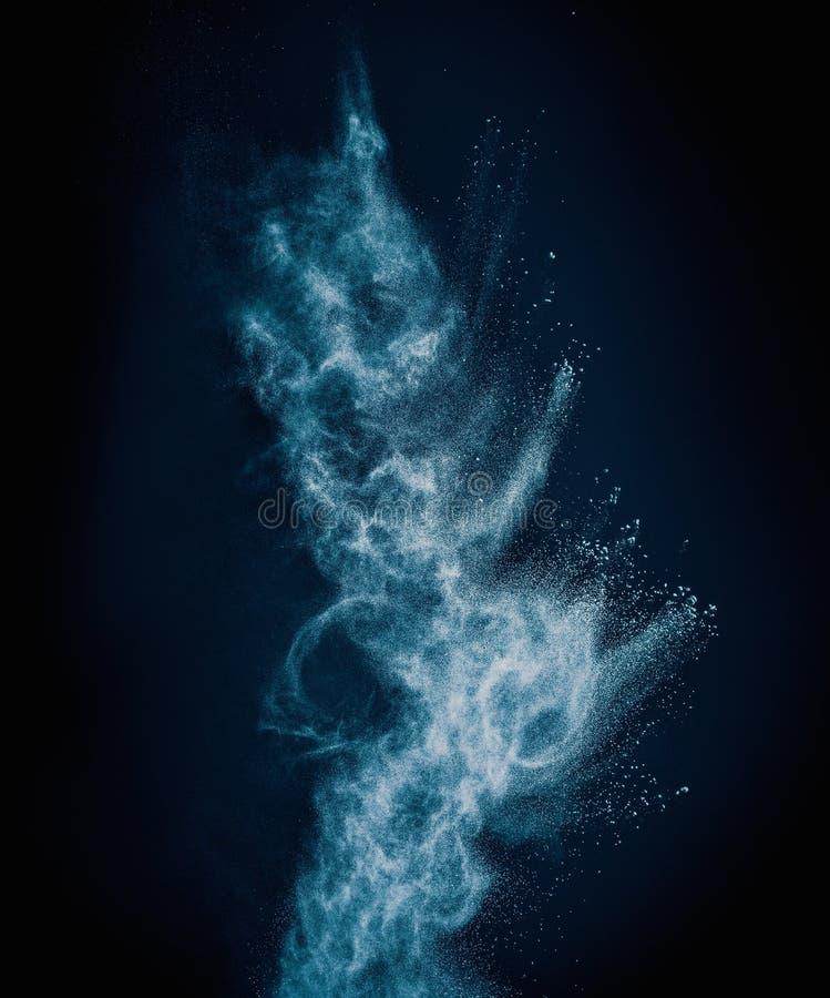 Blue powder exploding. Isolated on black royalty free stock images