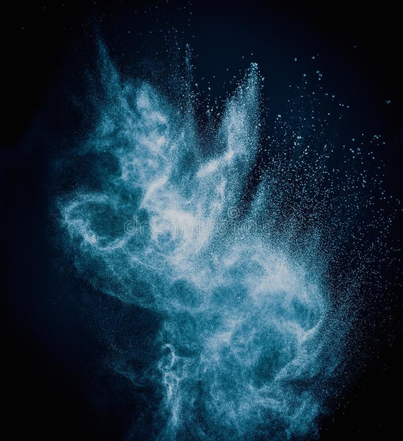Blue powder exploding. Isolated on black stock photos