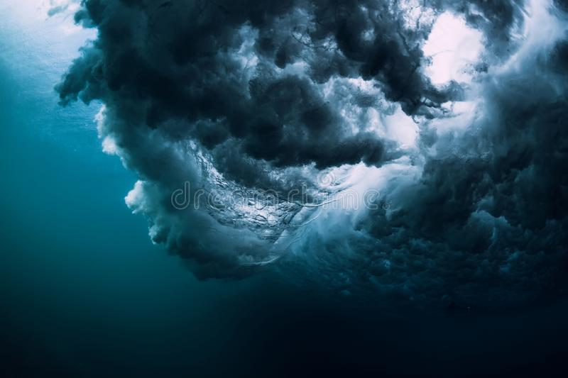 Blue powerful wave crashing in ocean. Underwater wave with foam and air bubbles stock photo