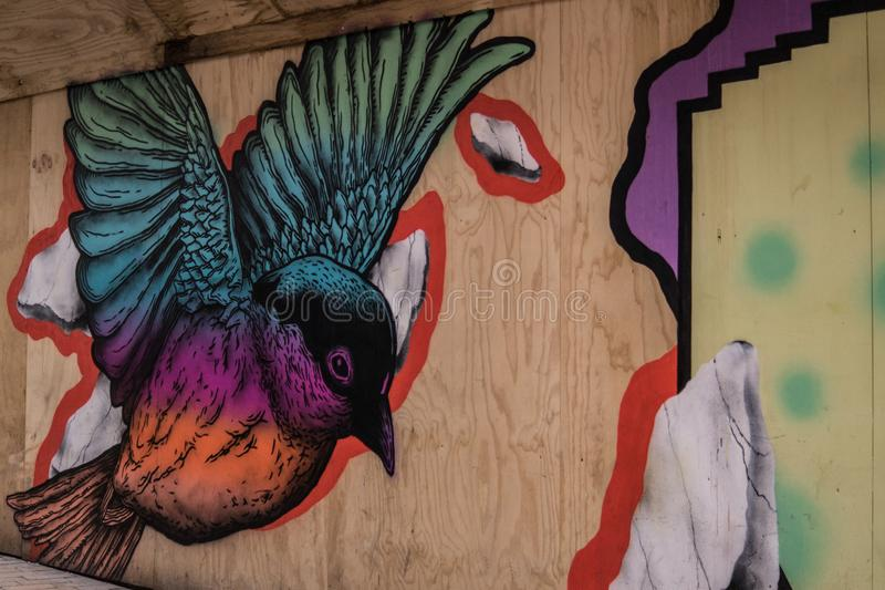 Blue Purple and Orange Bird Painted on Brown Wooden Panel royalty free stock photography