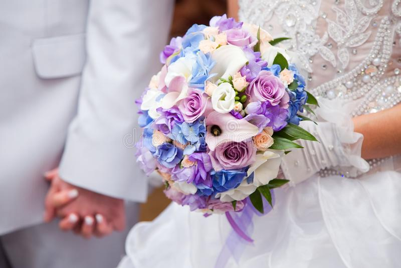 Blue and purple wedding bouqet. Beautiful blue and purple wedding bouqet in hands of bride stock image