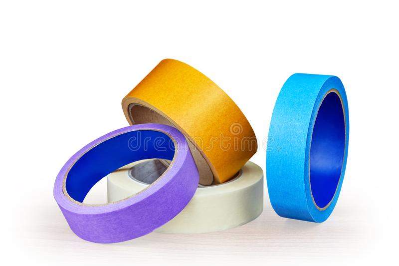 Blue, purple and yellow rollers of adhesive tape on white. stock images