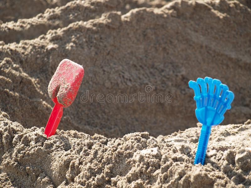Rake and shovel in the sand stock photography
