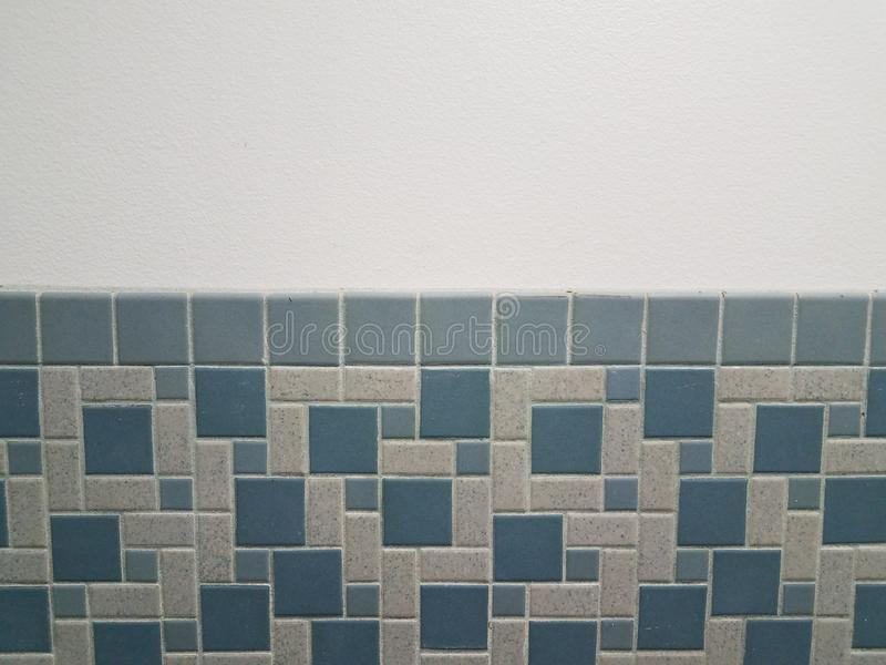 Blue rectangle and square tiles on bathroom wall royalty free stock images