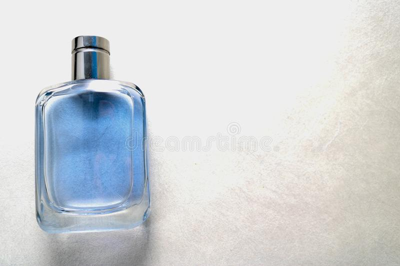 Blue rectangular beautiful glass transparent shiny fashionable glamorous bottle of cologne, perfume with silvery bezel and place f royalty free stock photo