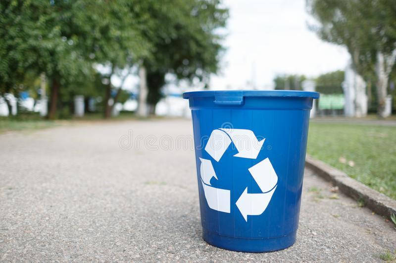 Bright recycle bin with label on the road without people. Concept of envirometal protection. Cleaned outside terrain. Blue recycle bin on asphalt road with royalty free stock photos