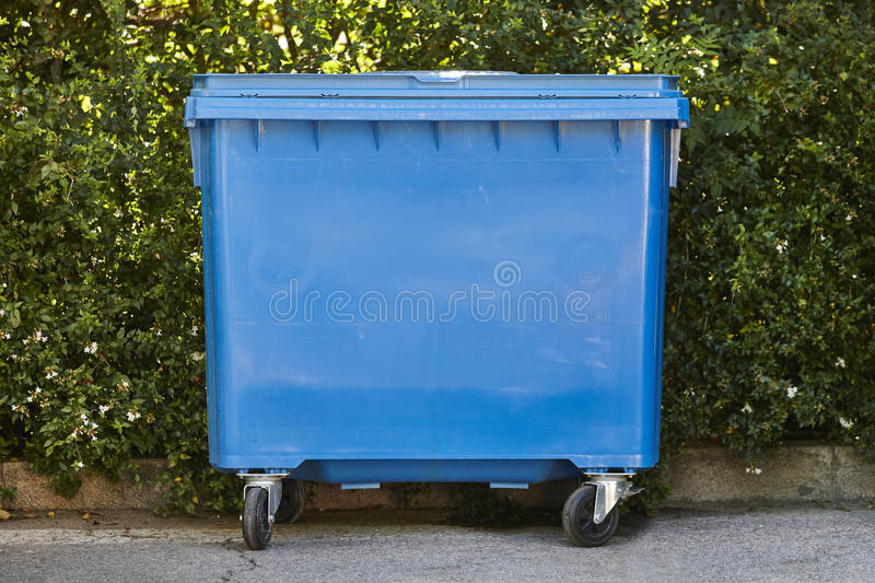 Blue recycling container for paper with green bush background. Environment royalty free stock photography
