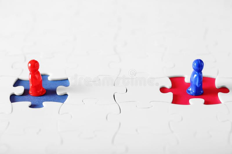 On a blue and red background white puzzles with missing piece stock photos