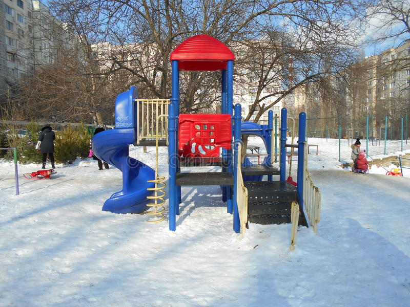 Blue and red children's slide in the snow park area of the city stock photography