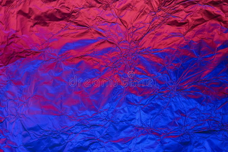 Blue red deformed background made of neon lights foil. Trendy duotone texture stock photo