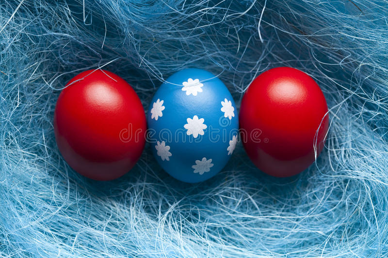Blue and red Easter eggs on blue background. One blue Easter egg and red eggs on blue background royalty free stock photos