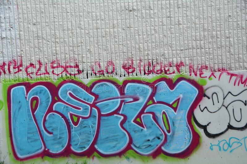 Blue and red graffiti word in SE Portland, Oregon. This is blue and red graffiti decorating a building wall in SE Portland, Oregon`s industrial area stock photography