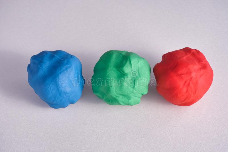 Blue, red and green moulds of plasticine on a grey surface. Close up royalty free stock image