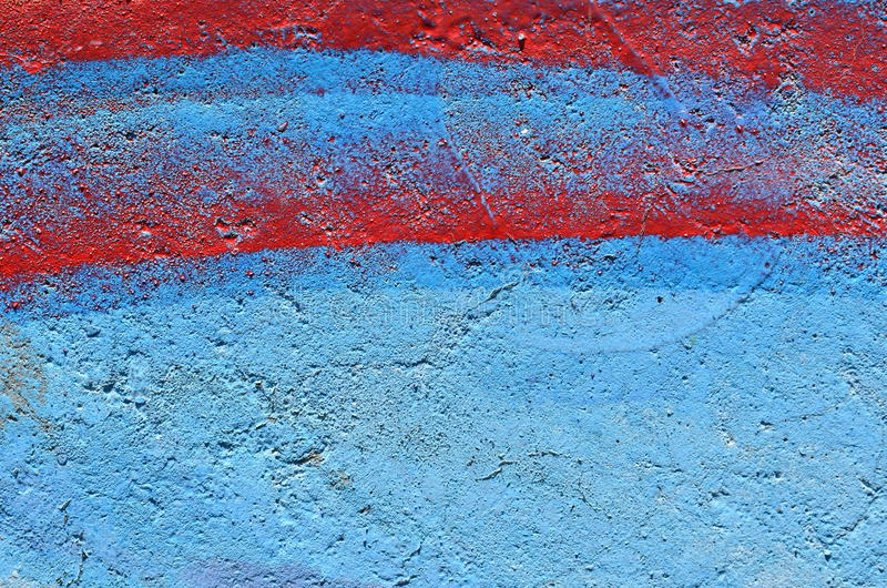 Red stripes on blue graffiti background. Rough concrete wall airbrushed with blue and red graffiti paint stock image