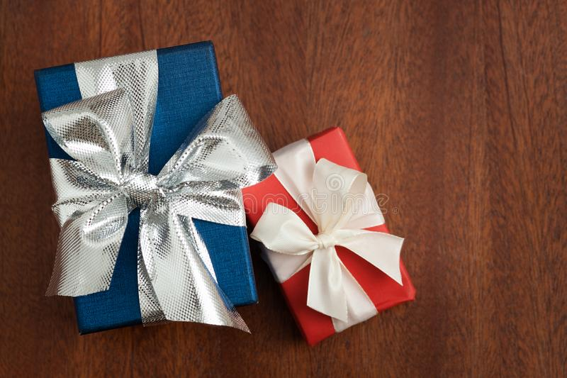 A blue and a red present with silver and white bow on a wooden board. royalty free stock images