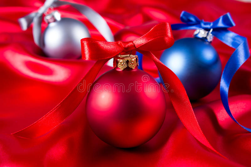 Blue, red and silver christmas balls on a silk cloth royalty free stock images
