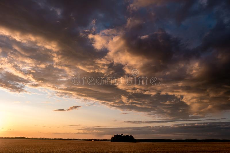 Blue red sky background with evening fluffy curly rolling clouds with setting sun. Good windy weather.  royalty free stock photos