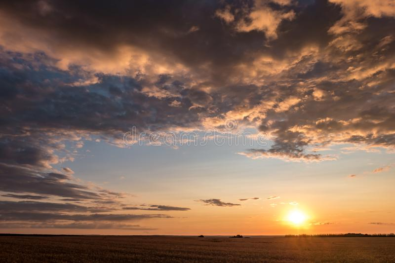 Blue red sky background with evening fluffy curly rolling clouds with setting sun. Good windy weather.  royalty free stock images