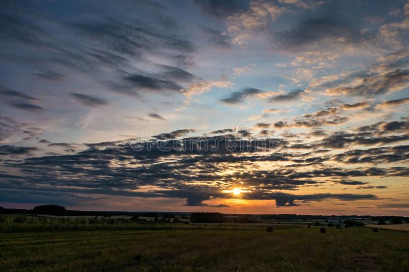 Blue red sky background with evening fluffy curly rolling clouds with setting sun. Good windy weather.  royalty free stock photo