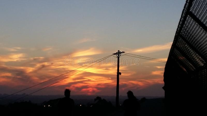 A blue and red sky with sun setting and silhouette stock photo
