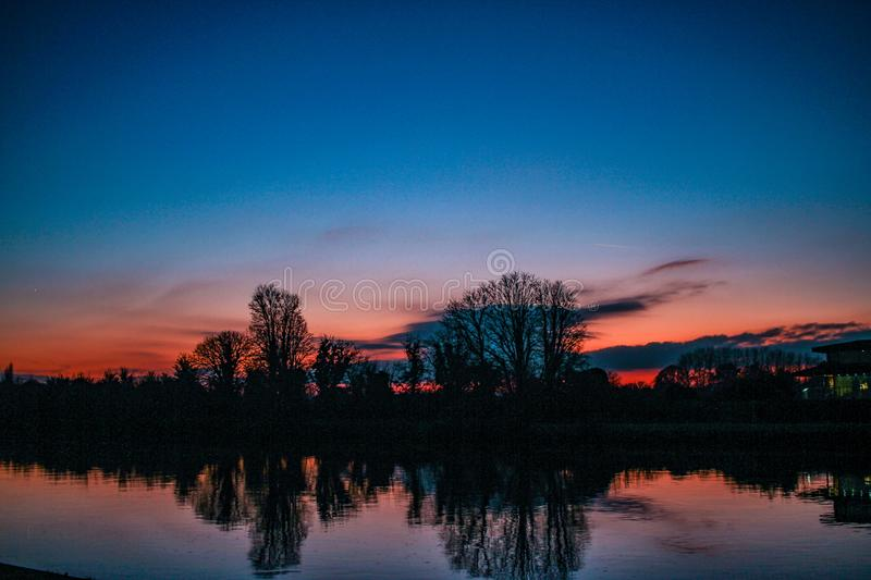 Blue and red sunset near Kingston upon Thames in England in December. Trees in silhouette reflected in the River Thames. A vignetted clear winter sky stock images