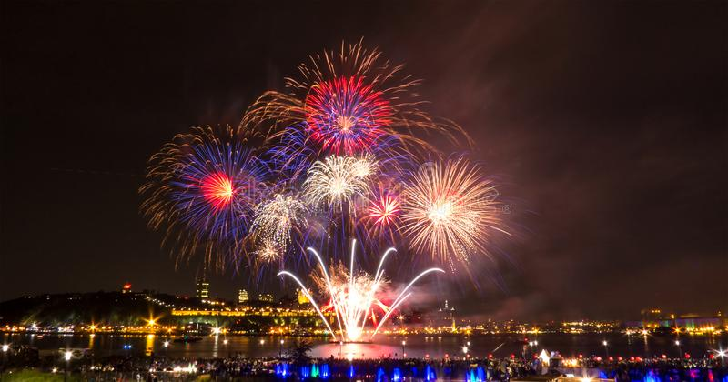 Blue, red, and white fireworks over the Saint-Lawrence River royalty free stock image