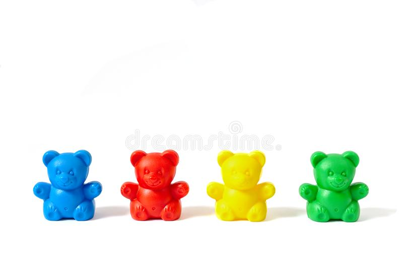 Blue, red, yellow and green plastic toy bears isolated on white background. Small blue, red, yellow and green plastic toy bears isolated on white background royalty free stock image