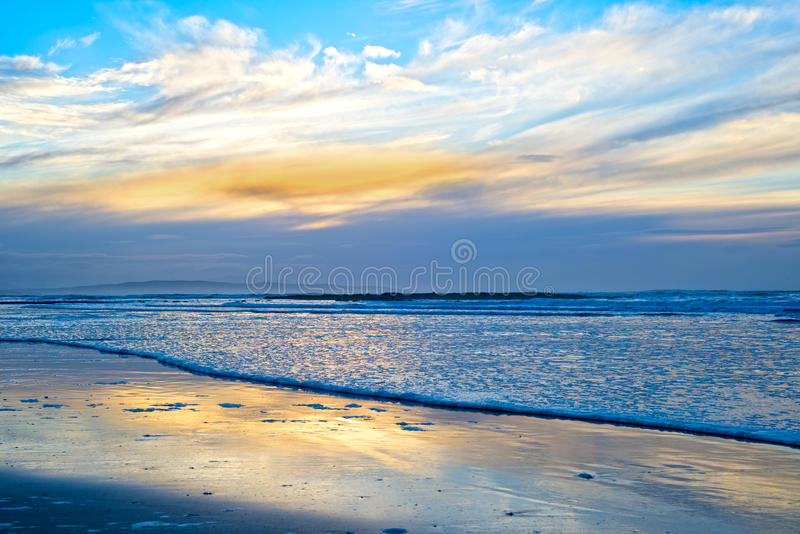 Blue reflections and calm waves. Reflections and calm waves crashing onto the beach at ballybunion in ireland stock photography