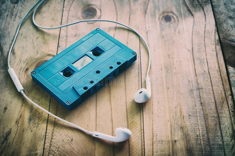 Blue retro cassette tape and white earphone on wooden table. Added color filler, vintage and retro effect stock photos
