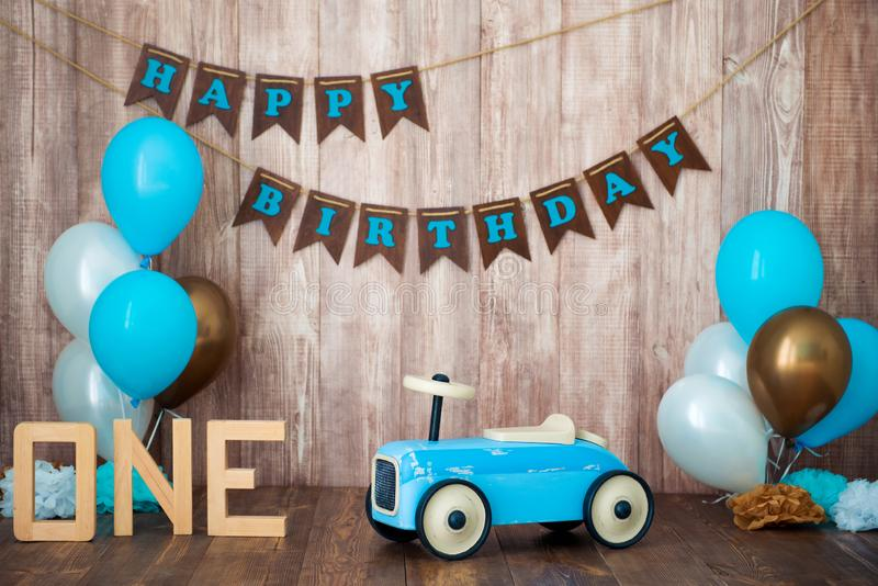 Blue retro toy car with helium balloons on a wooden background. Children`s holiday decorated photo zone for a little boy. Happy royalty free stock photos