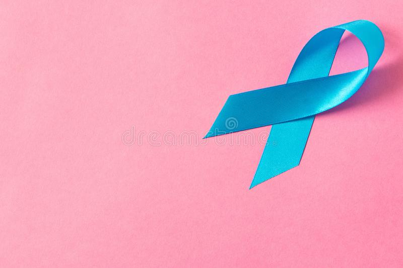 Blue ribbon. Isolated on pink background with empty space for text. Close up stock photo