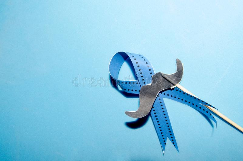 Blue ribbon with moustache on blue background. Prostate cancer awareness month concept royalty free stock photography
